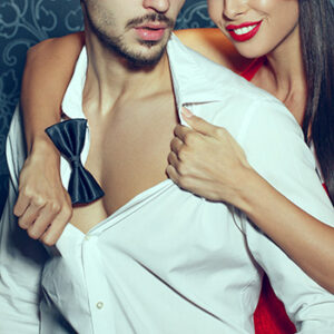 Sexy woman with red lips undressing trendy macho man indoor, foreplay