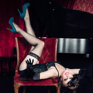 A burlesque dancer poses on a chair in front of a grand piano.